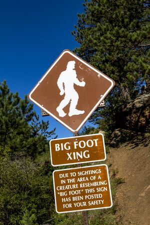 xing: Big foot crossing sign with warning about sightings in the area Stock Photo