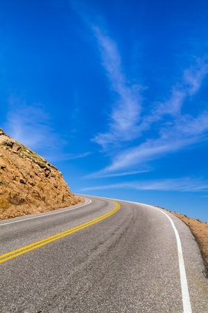 blacktop: Mountain road appearing to disappear into the sky Stock Photo