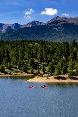 Two kayakers in red kayaks paddling on high mountain lake with scenic shoreline and mountains in distance on summer morning