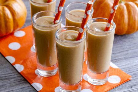 shooters: Close up of fresh pumpkin coconut smoothies shooters on orange polka dot napkins and straws sitting on wooden table