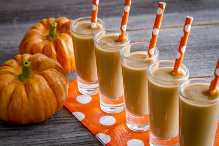 shooters: Row of five fresh pumpkin coconut smoothies shooters on orange polka dot napkins and straws Stock Photo