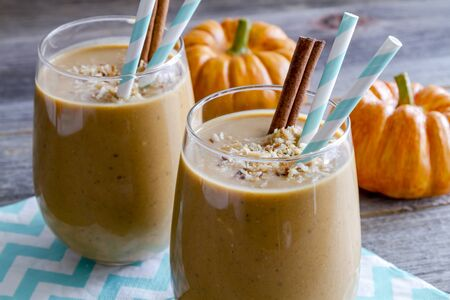 Fresh pumpkin coconut smoothies garnished with toasted coconut sitting on blue chevron napkin and blue swirled straws and cinnamon sticks