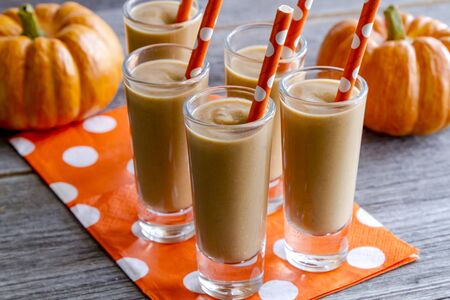 Fresh pumpkin coconut smoothies shooters on orange polka dot napkins and straws sitting on wooden table