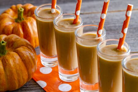 shooters: Close up of row of five fresh pumpkin coconut smoothies shooters on orange polka dot napkins and straws sitting on wooden table