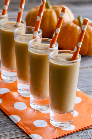 shooters: Row of fresh pumpkin coconut smoothies shooters on orange polka dot napkins and straws sitting on wooden table