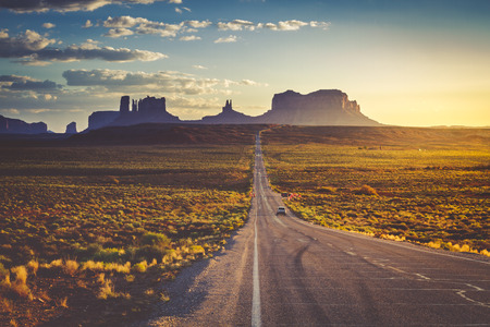Bright sunset along stretch of highway at Utah Arizona border known as Forest Gump Point and entrance to Monument Valley Navajo Tribal Park Imagens - 64049662