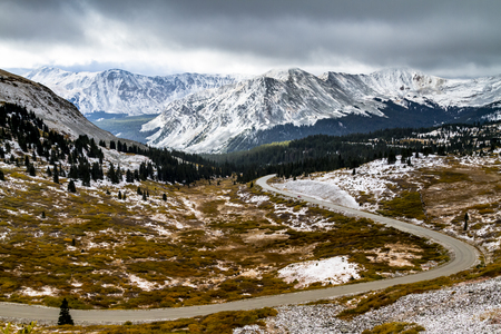 aspen tree: Cottonwood pass overlook of curvy mountain pass road looking at snow covered peaks and storm clouds in the distance