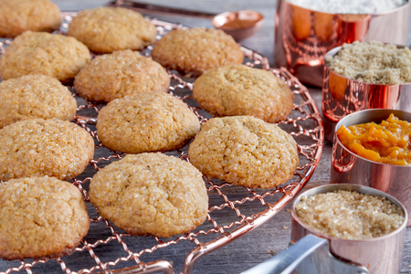 Fresh baked pumpkin spice cookies sitting on copper wire cooling rack surrounded by ingredients in copper measuring cups and spoon