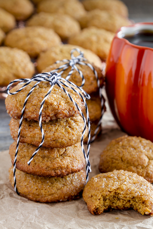 Stack of fresh baked pumpkin spice cookies tied with black and white bakers twine with coffee in pumpkin shaped mug Stock Photo