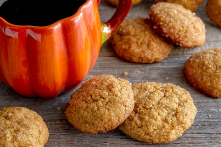 fresh baked: Fresh baked pumpkin spice cookies sitting on rustic wooden table with cup of coffee in pumpkin shaped mug Stock Photo