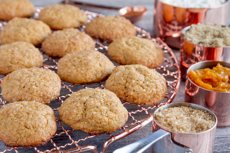 fresh baked: Fresh baked pumpkin spice cookies sitting on copper wire cooling rack surrounded by ingredients in copper measuring cups and spoon
