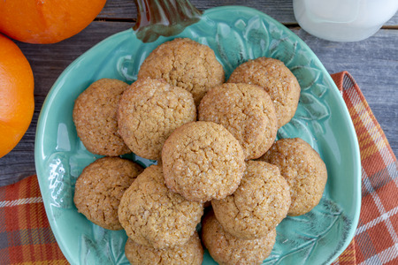 fresh baked: Close up of fresh baked pumpkin spice cookies sitting on blue pumpkin shaped plate with glass of milk and two fresh small pumpkins sitting on orange checkered napkin Stock Photo