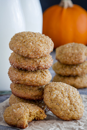 fresh baked: Stack of fresh baked pumpkin spice cookies with two glasses of milk and fresh pumpkin in background