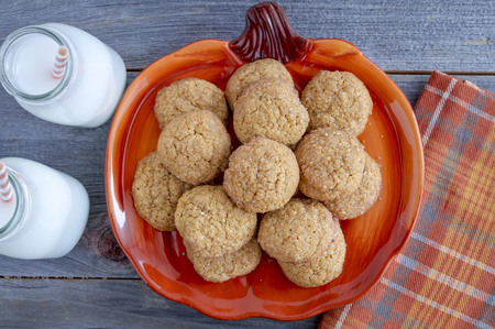 fresh baked: Close up of fresh baked pumpkin spice cookies sitting on orange pumpkin shaped plate with two glasses of milk and an orange checkered napkin