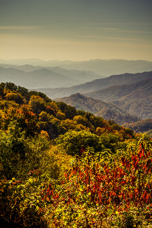 Colorful mountainside of fall foliage with mountain layers in distance at Great Smoky Mountain National Park Stock Photo