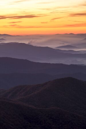great smokies: Hazy mountain layers and fog with dramatic sunrise sky at Clingmans Dome in Great Smoky Mountains National Park