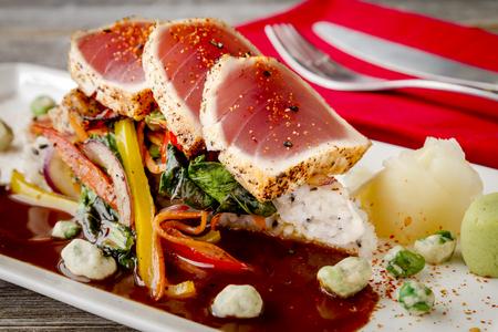 bok choy: Plate of seared rare Ahi tuna slices sitting on Jasmine rice with bok choy stir fry vegetables and wasabi peas
