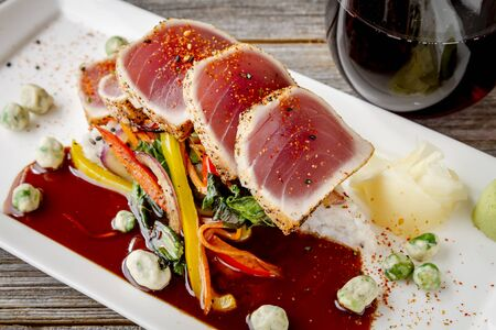 bok choy: Plate of rare seared Ahi tuna slices with bok choy stir fry vegetables and wasabi peas and glass of wine on side