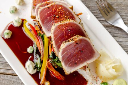 bok choy: Close up of rare seared Ahi tuna slices with bok choy stir fry vegetables and wasabi peas on white plate with fork on side