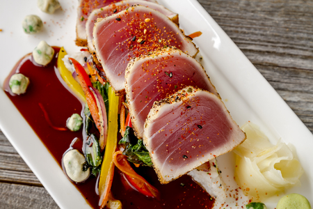 bok choy: Close up of rare seared Ahi tuna slices with bok choy stir fry vegetables and wasabi peas on white plate from above