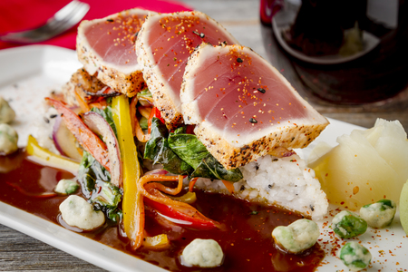 bok choy: Close up of seared rare Ahi tuna slices with bok choy stir fry vegetables sitting on jasmine rice with glass of red wine and fork with napkin