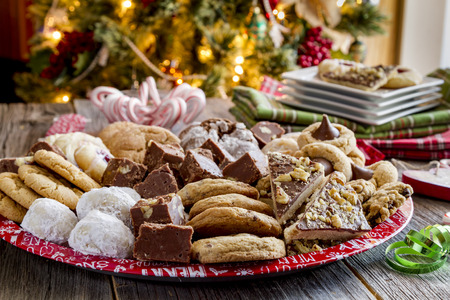Rustic holiday party table with tray of homemade cookies and candy with holiday napkins and plates in front of Christmas tree