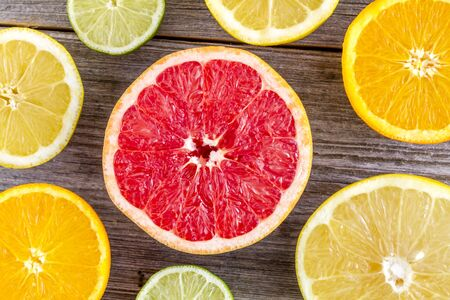 Close up of grapefruits, oranges, limes and lemons cut in half sitting on rustic wooden table