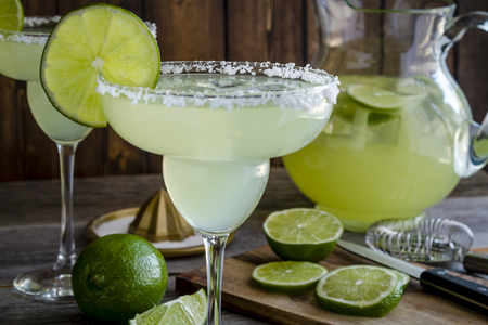 BARWARE: Close up of table filled with glasses and pitcher filled with classic lime margarita cocktails, fresh limes and barware