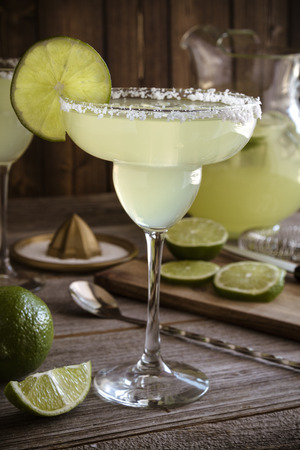 Table filled with glasses and pitcher filled with classic lime margarita alcoholic beverages