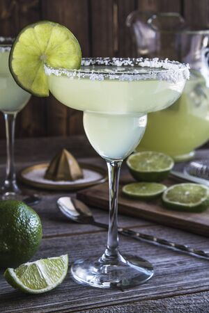 Classic lime margarita cocktails with pitcher, limes slices sitting on rustic wooden table