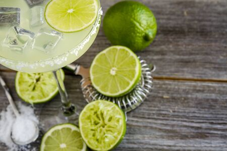 cocktail strainer: Fresh classic lime margarita cocktail sitting on rustic wooden table surrounded by fresh limes, hawthorne strainer and margarita salt