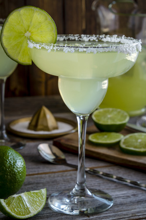 Close up of classic lime margarita cocktails with pitcher, limes slices sitting on rustic wooden table
