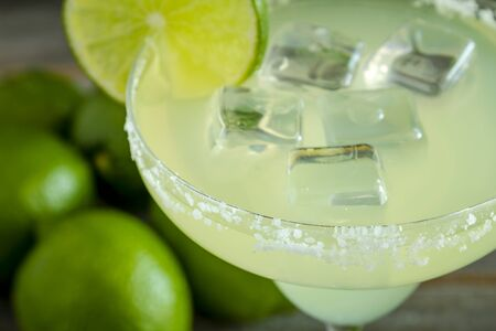 margaritas: Classic lime margarita cocktail with whole fresh limes in background