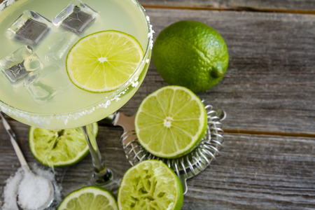 cocktail strainer: Close up of classic lime margarita cocktail sitting on rustic wooden table surrounded by fresh limes, hawthorne strainer and margarita salt