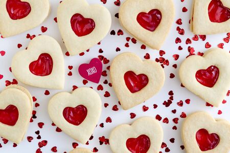 Heart shaped sugar cookies with heart cutout filled with strawberry jam and red heart with xoxo message Stock Photo
