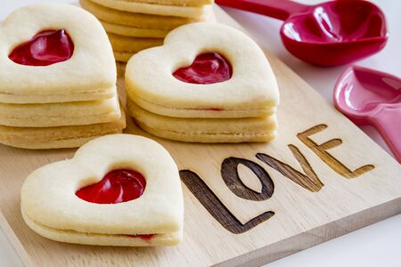 Heart shaped linzer cookies filled with strawberry jam sitting on wooden cutting board with word love etched in wood and measuring spoons in background Stock Photo