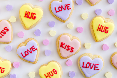 Close up of heart shaped sugar cookies with colorful frosting and hand written messages with candy hearts on white background
