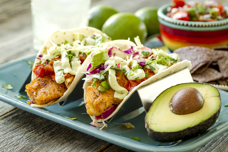 Fish tacos with fresh coleslaw, salsa, lime sour cream and avocado sitting on blue plate