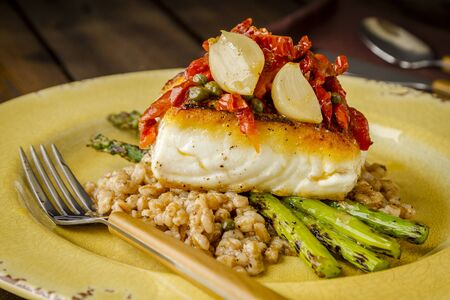 Dinner plate of fresh halibut fillet over bed farro with grilled asparagus, topped with salsa of red peppers, sundried tomatoes, garlic and capers on rustic yellow plate Stock Photo