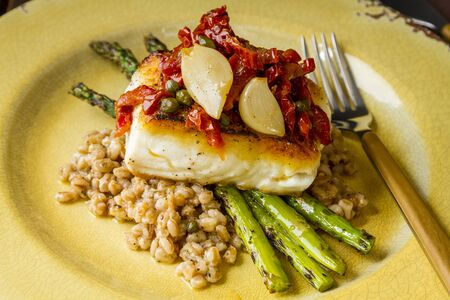 Pan seared halibut fillet over bed farro with grilled asparagus, topped with salsa of red peppers, sundried tomatoes, garlic and capers