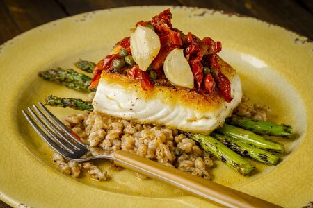 Fresh halibut fish fillet over bed farro with grilled asparagus, topped with salsa of red peppers, sundried tomatoes, garlic and capers sitting on rustic yellow plate with folk