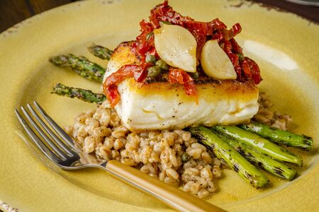Close up of fresh halibut fillet over bed farro with grilled asparagus, topped with salsa of red peppers, sundried tomatoes, garlic and capers sitting on rustic yellow plate