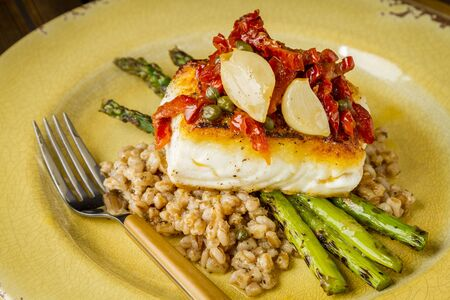 Halibut fillet over bed farro with grilled asparagus, topped with salsa of red peppers, sundried tomatoes, garlic and capers sitting on rustic yellow plate Stock Photo