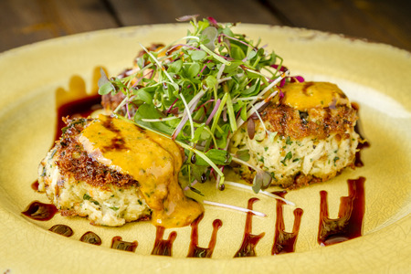 Three pan seared blue crab cakes topped with roasted tomato basil aioli and micro green with balsamic glaze Stock Photo