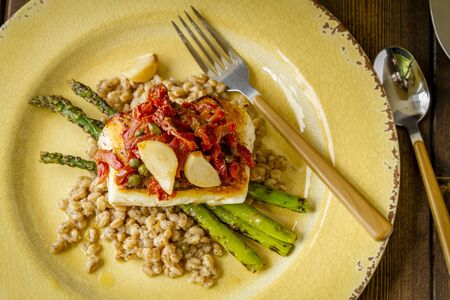Fresh halibut fillet over bed farro with grilled asparagus, topped with salsa of red peppers, sundried tomatoes, garlic and capers sitting on rustic yellow plate with folk shot from above