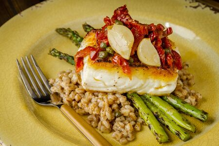 Halibut fillet on bed farro with grilled asparagus, topped with salsa of red peppers, sundried tomatoes, garlic and capers sitting on rustic yellow plate with wooden folk Stock Photo