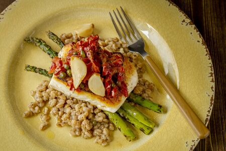 Shot from above plate of halibut fish fillet over bed farro with grilled asparagus, topped with salsa of red peppers, sundried tomatoes, garlic and capers sitting on rustic yellow plate with wooden folk