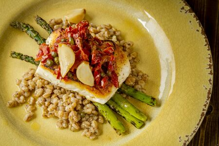 Shot from above plate of fresh halibut fish fillet over bed farro with grilled asparagus, topped with salsa of red peppers, sundried tomatoes, garlic and capers sitting on rustic yellow plate