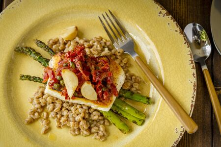 Shot from above plate of fresh halibut fish fillet over bed farro with grilled asparagus, topped with salsa of red peppers, sundried tomatoes, garlic and capers sitting on rustic yellow plate with folk
