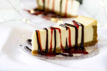 Closse up display of single slices of cheesecake with chocolate and strawberry sauce drizzled on top Stock Photo